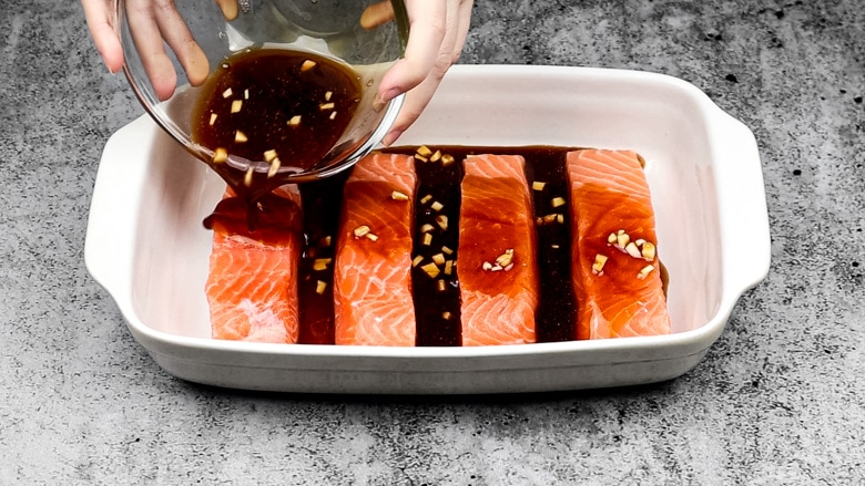 Pouring maple sauce over salmon in baking dish.