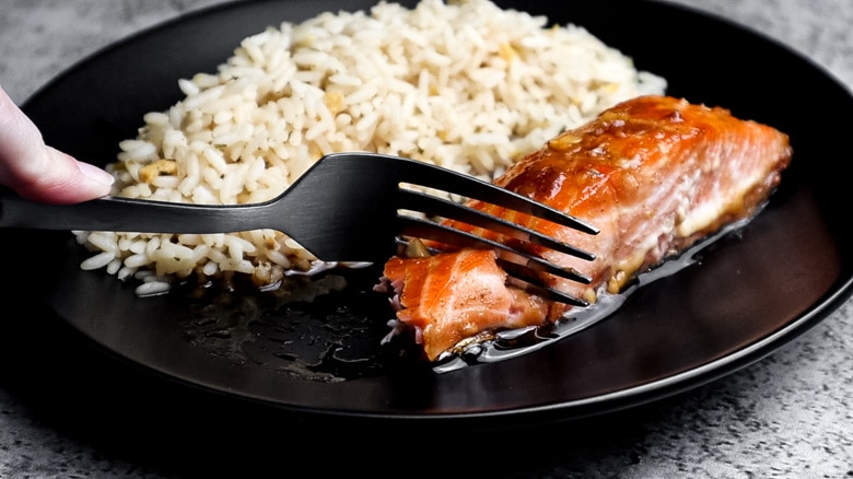 Salmon and rice served on a plate with a fork.